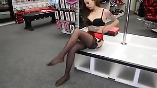 Tattooed girl in red belt  stockings and high heels posed.